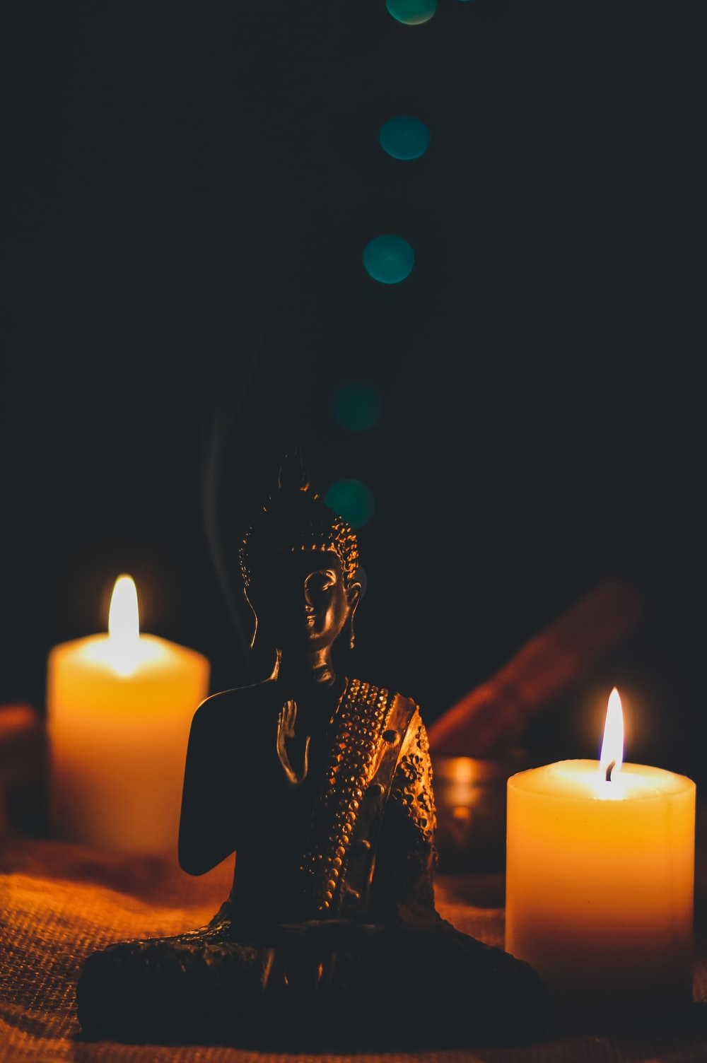 sitting buddha beside pillar candles