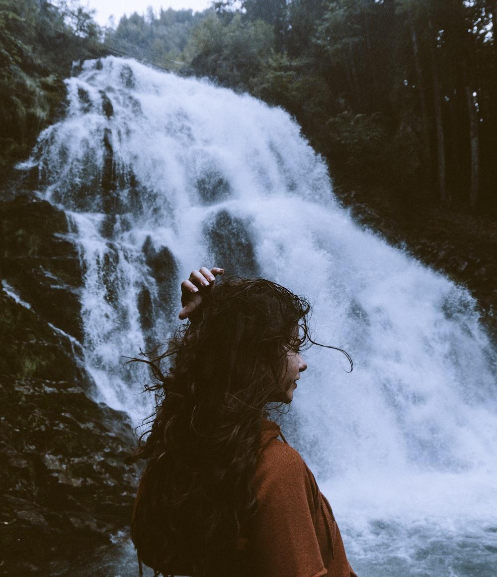 woman in brown shirt near waterfalls at daytime