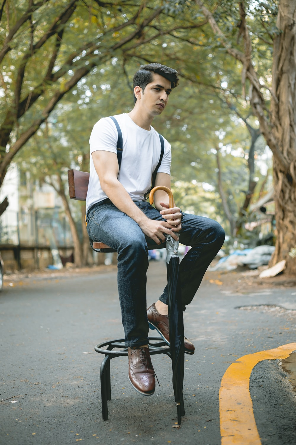 man in white crew-neck T-shirt and blue denim jeans sitting on stool holding black umbrella