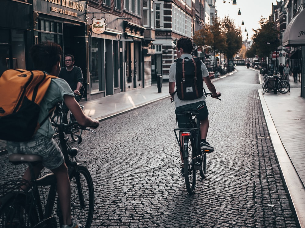 two person riding bicycle on street near buildings