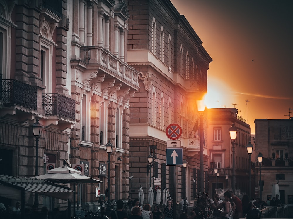 people on road beside buildings during golden hour
