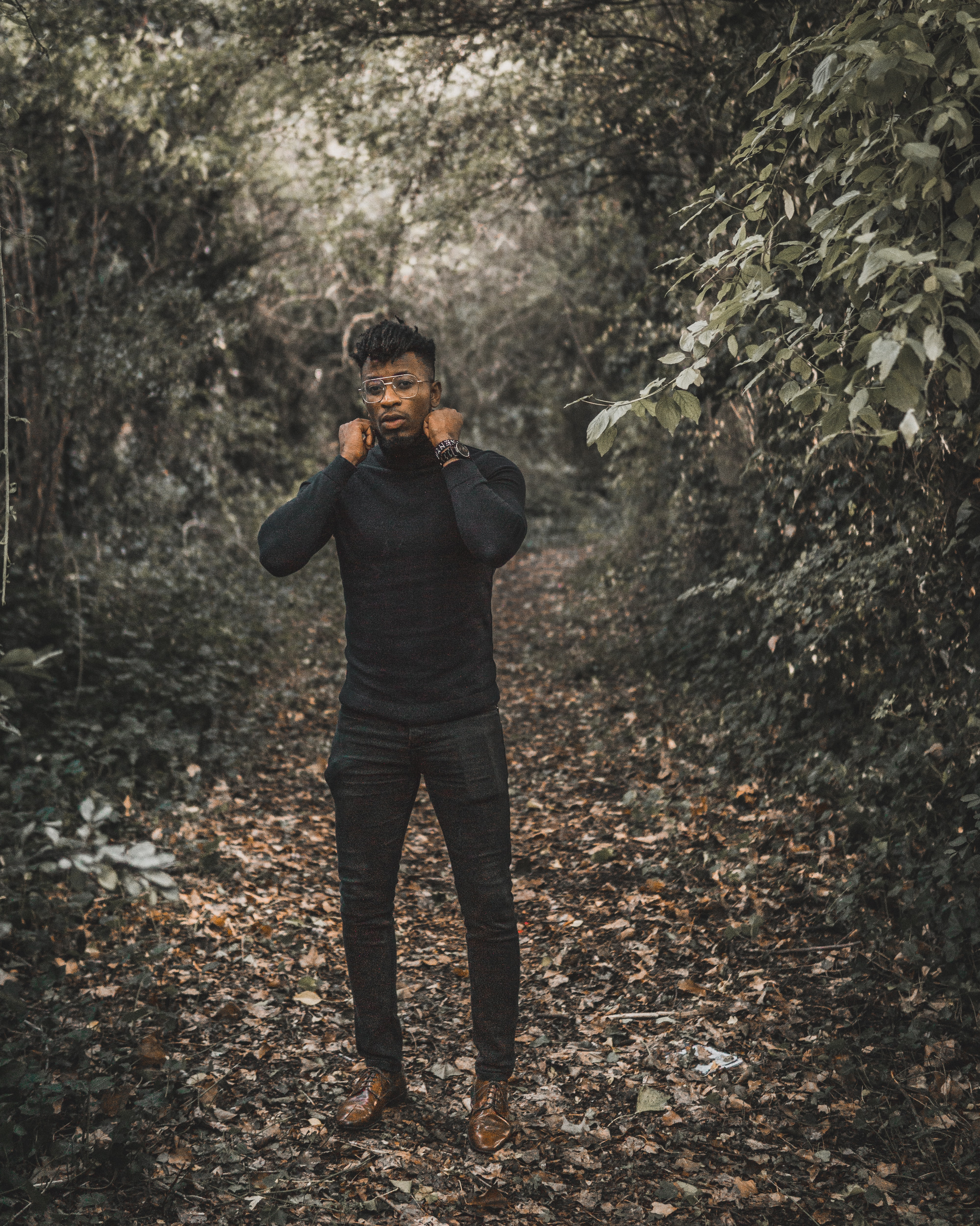 standing man wearing black turtleneck sweater and black fitted pants surrounded with trees during daytime