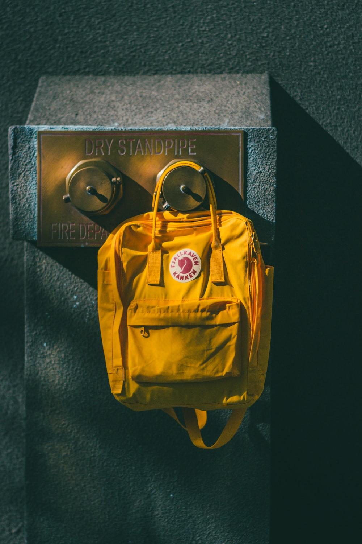 yellow backpack hanging on brown wall leg shelf