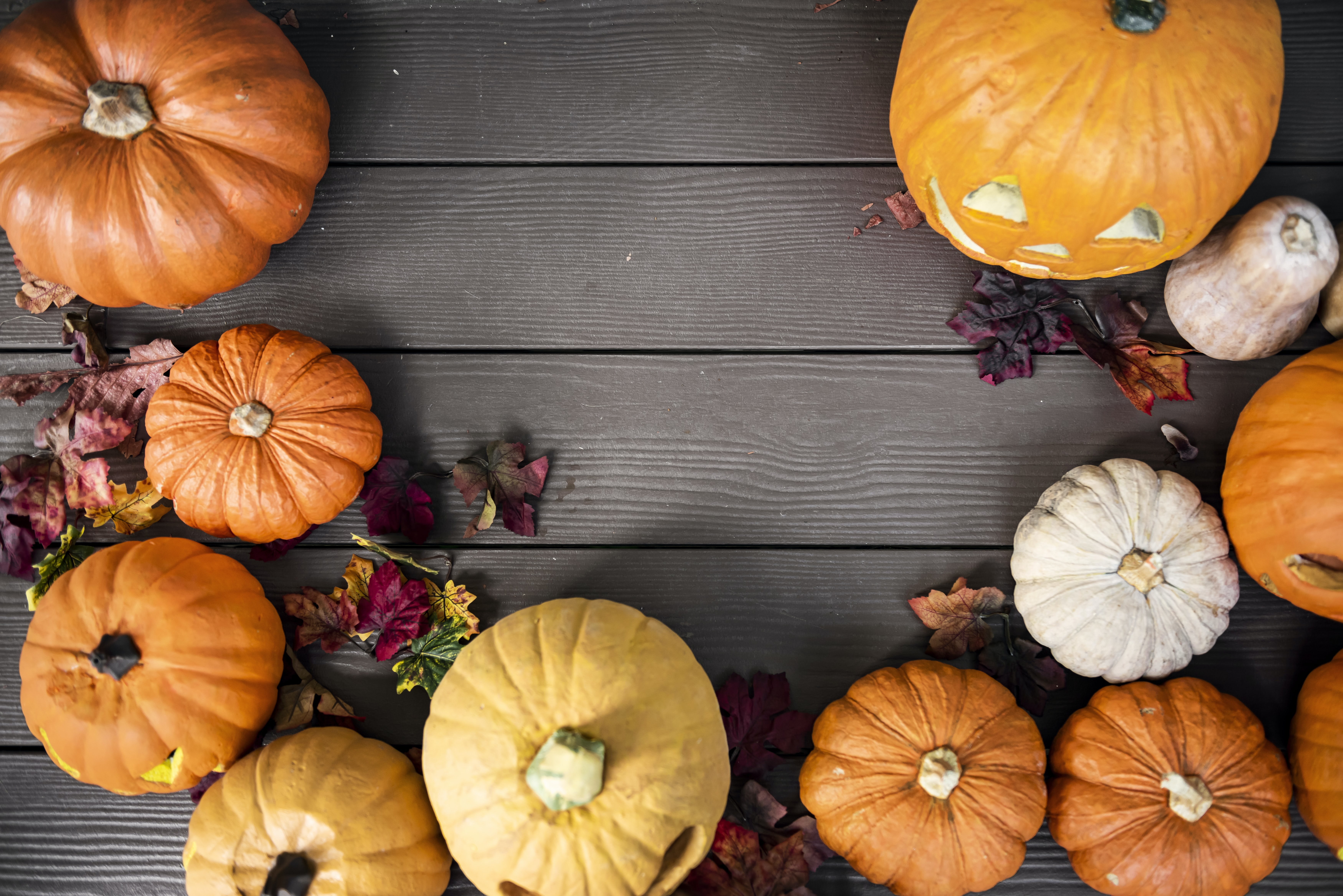 orange pumpkins surrounded by leaves on brown wooden surface