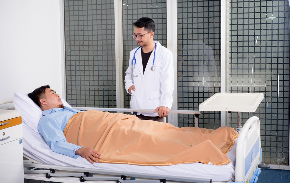 man lying on bed talking to doctor
