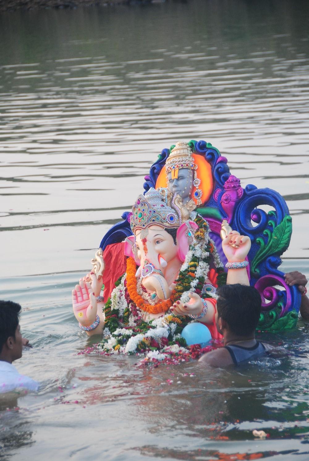 person holding hindu deity figurine