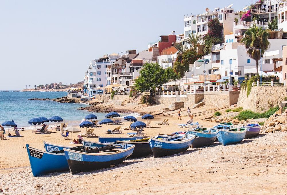 blue boats in beach near city