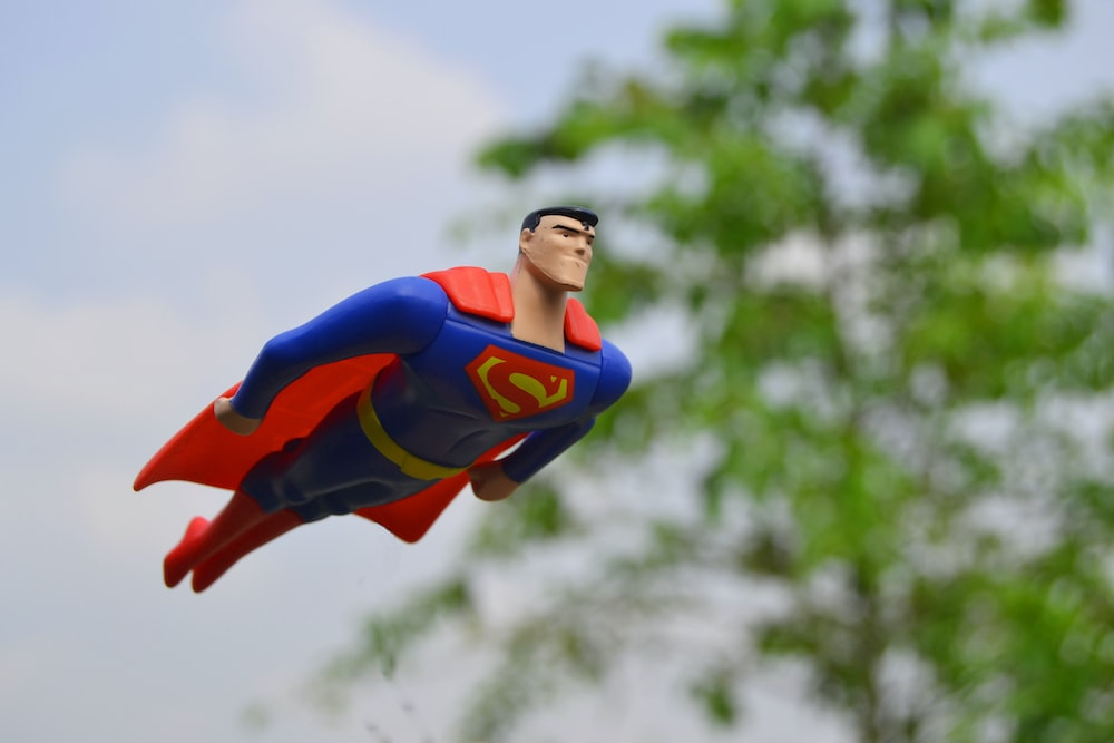 Superman flying near green grass
