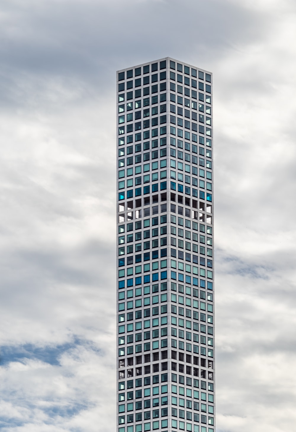high-rise mirror building under white clouds