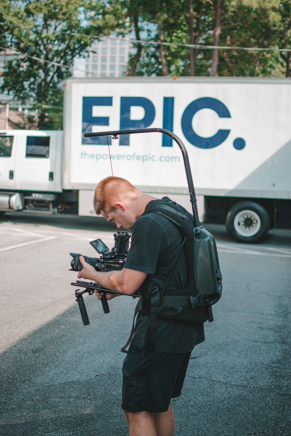 man taking photo near Epic truck