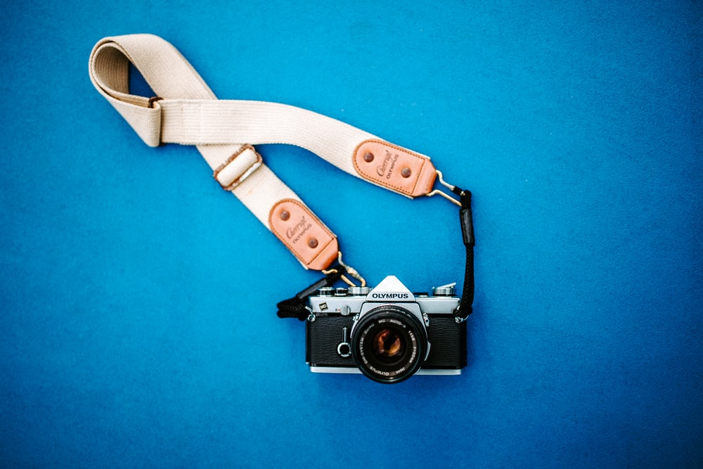 black SLR camera with white strap