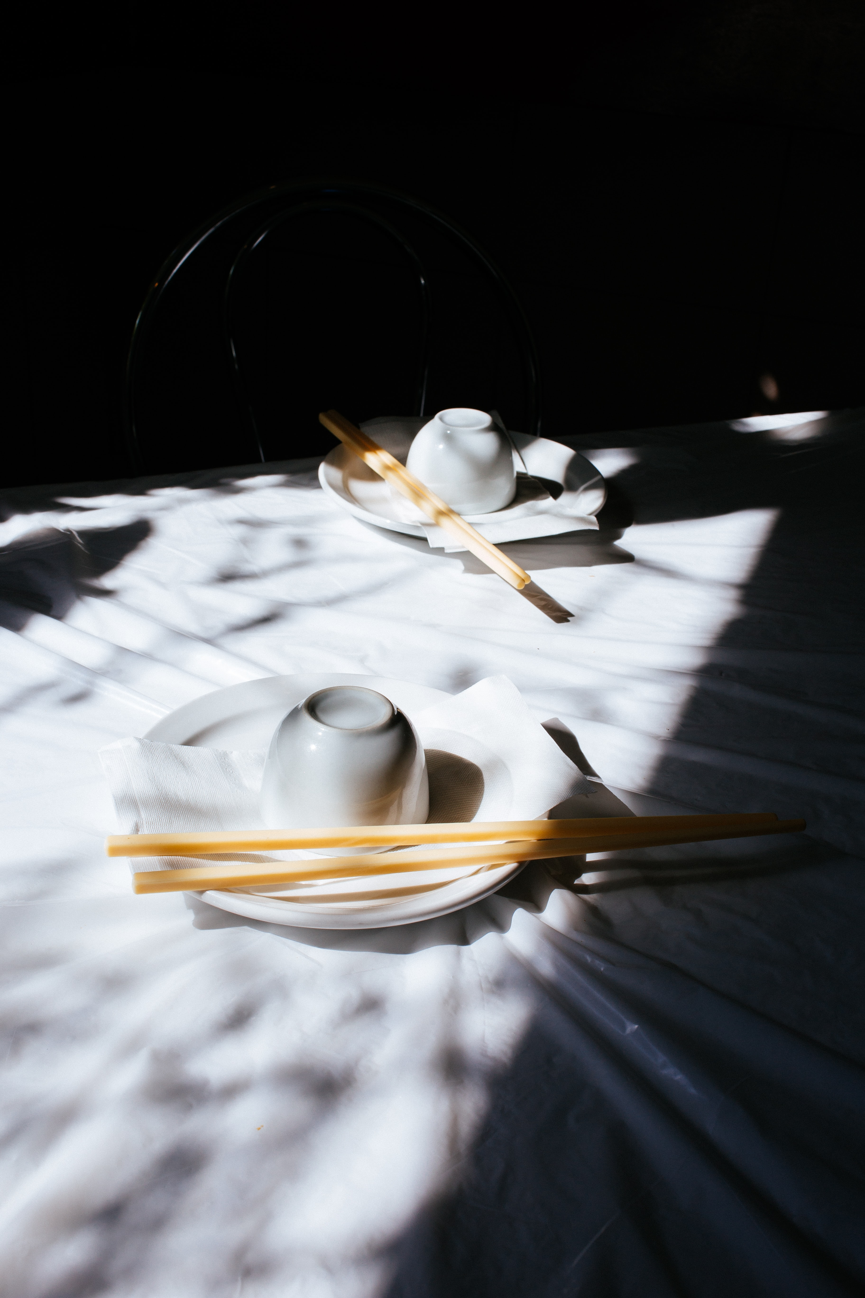white ceramic teacup and saucer on white tablecloth