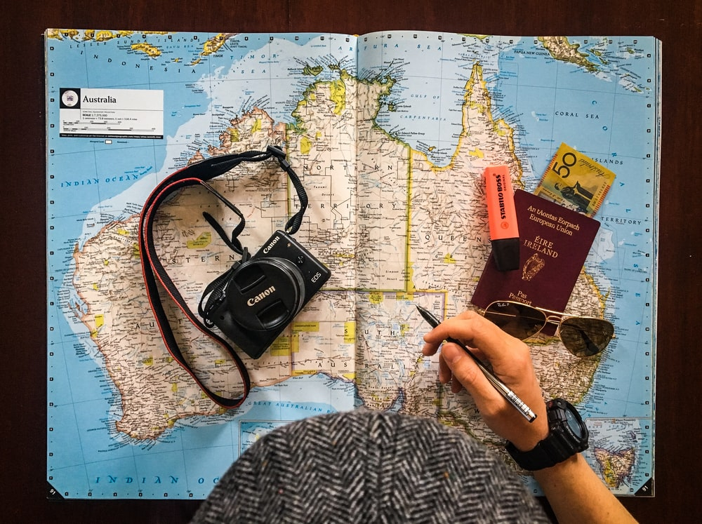flat lay photography of person holding pen in front of world map