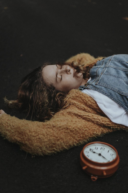 woman lying on floor near alarm clock