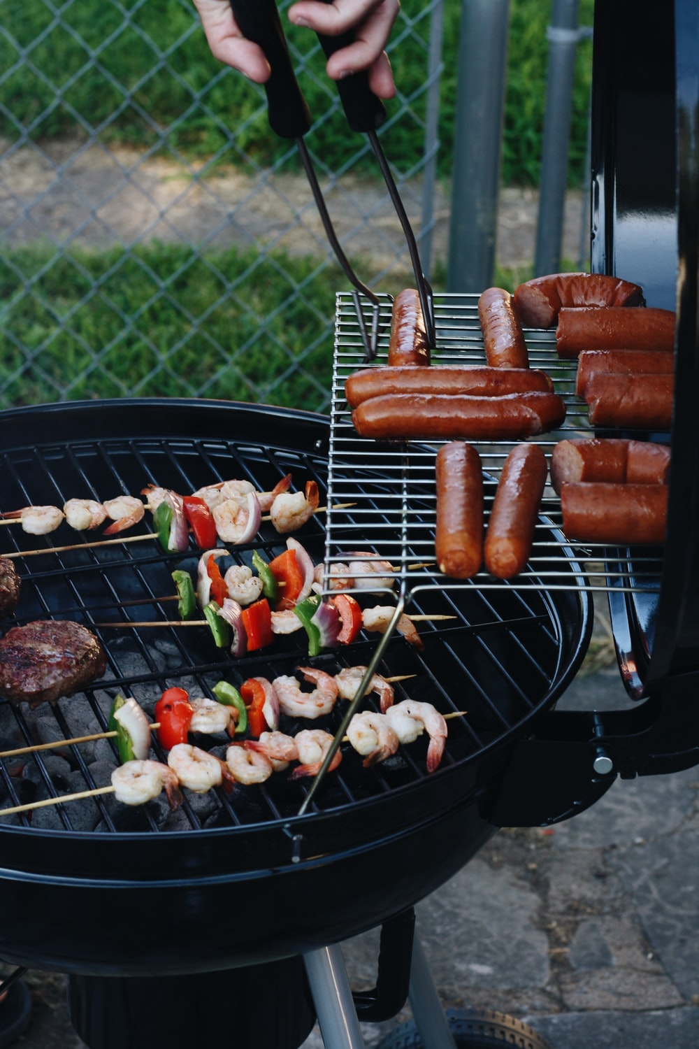 grilled sausage and meat beside gray chain-link fence