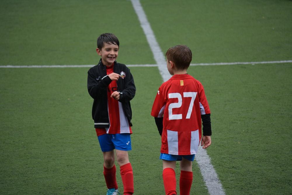 two boy standing on soccer field