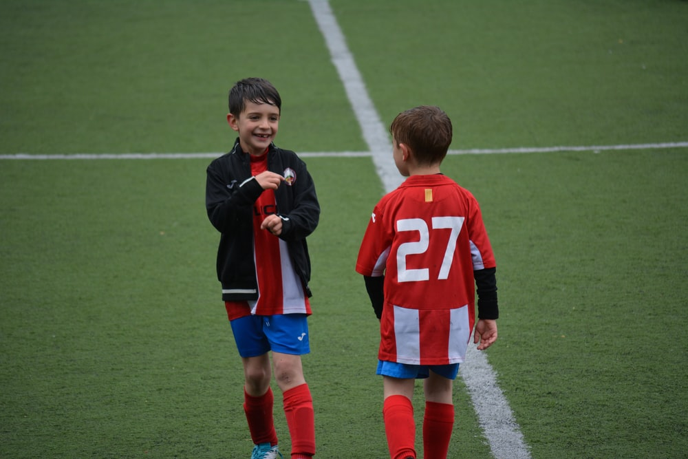 two boy standing on soccer field
