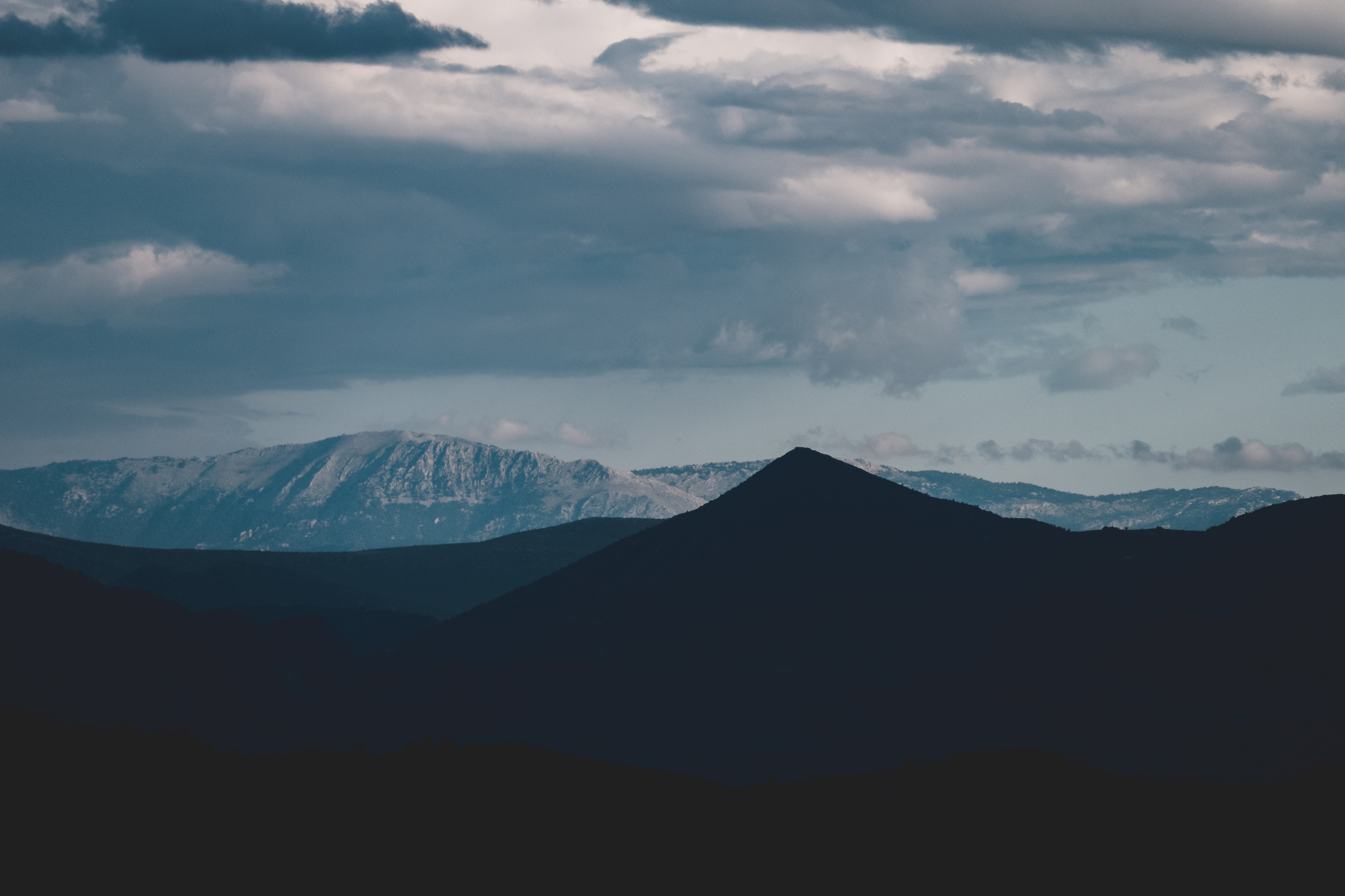 silhouette of mountain under white cloudy sky