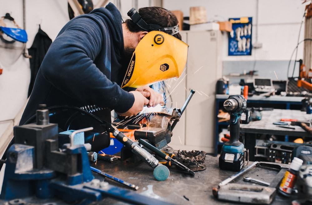 man wearing black hoodie using welding tool