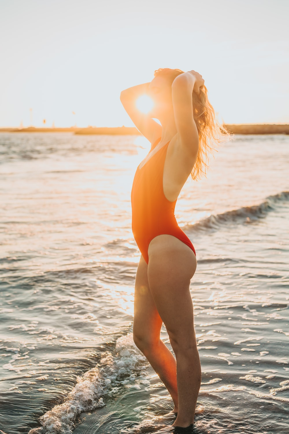 woman wearing red one-piece swimsuit standing on beach water