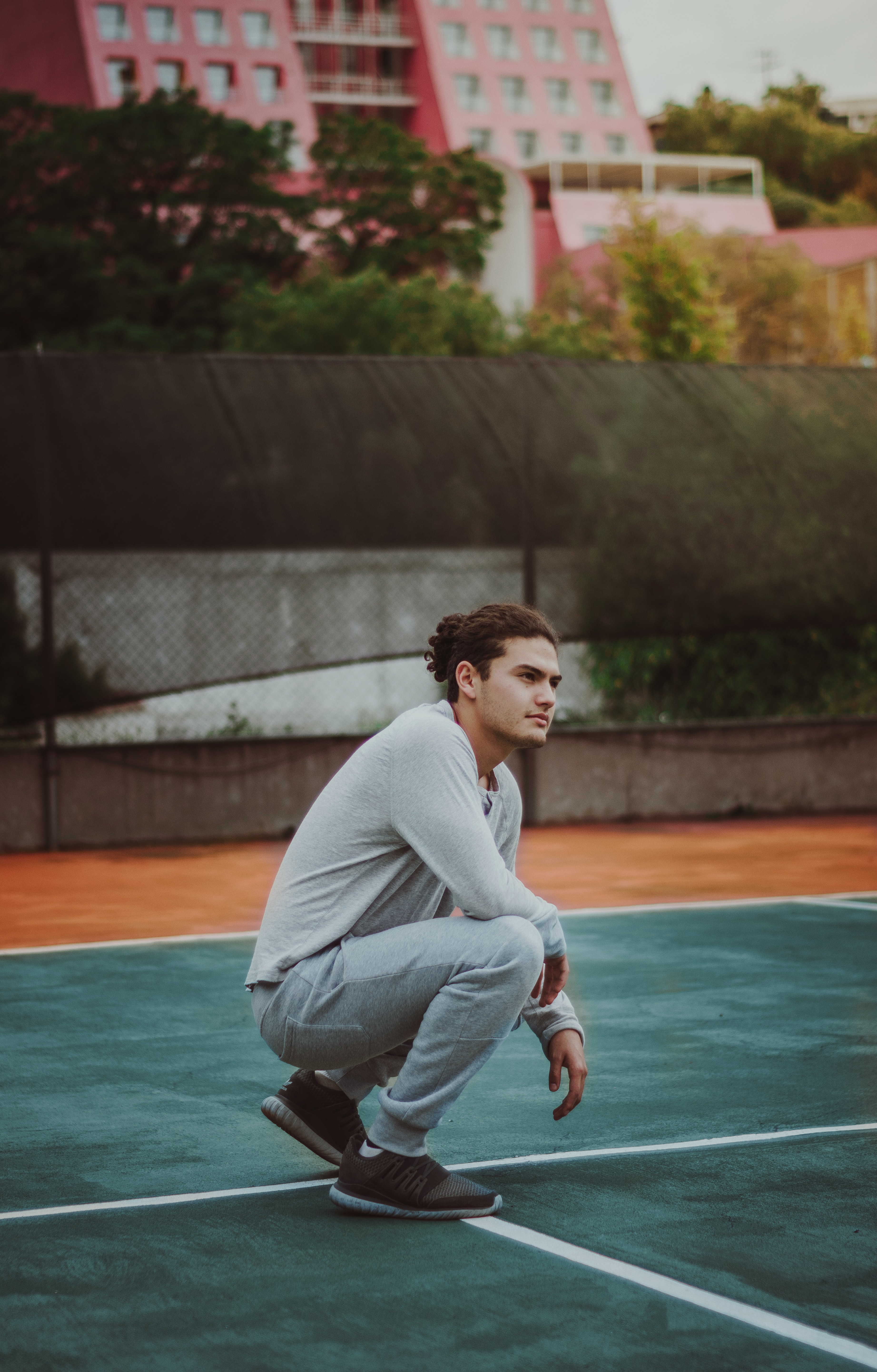 man squatting on court during day