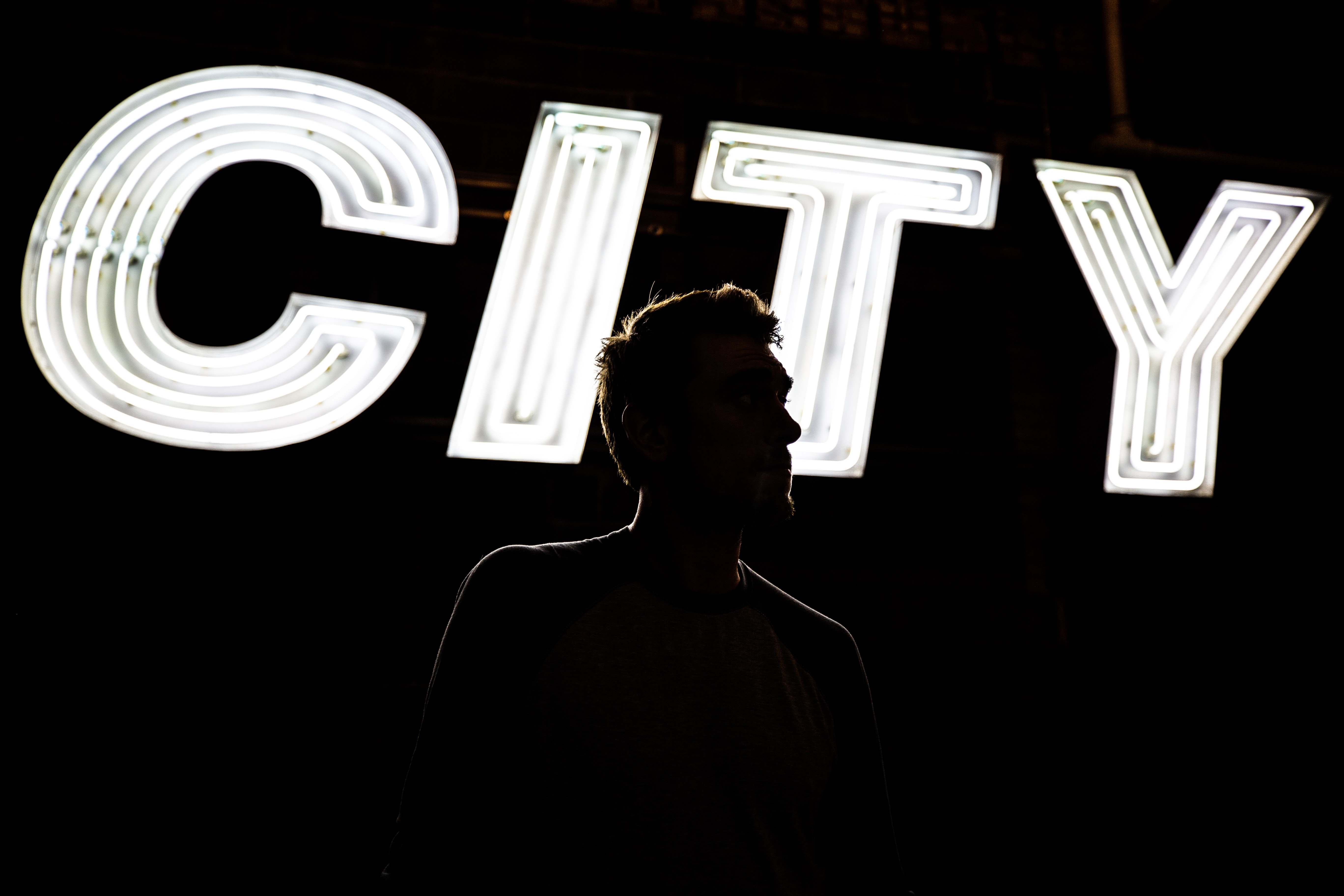man standing in front of CITY light signage
