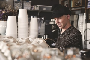 smiling man beside cups