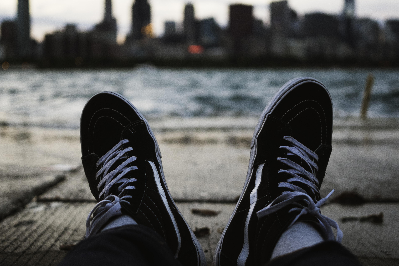 person wearing black Vans Sk8-Hi sitting on bay near river during daytime