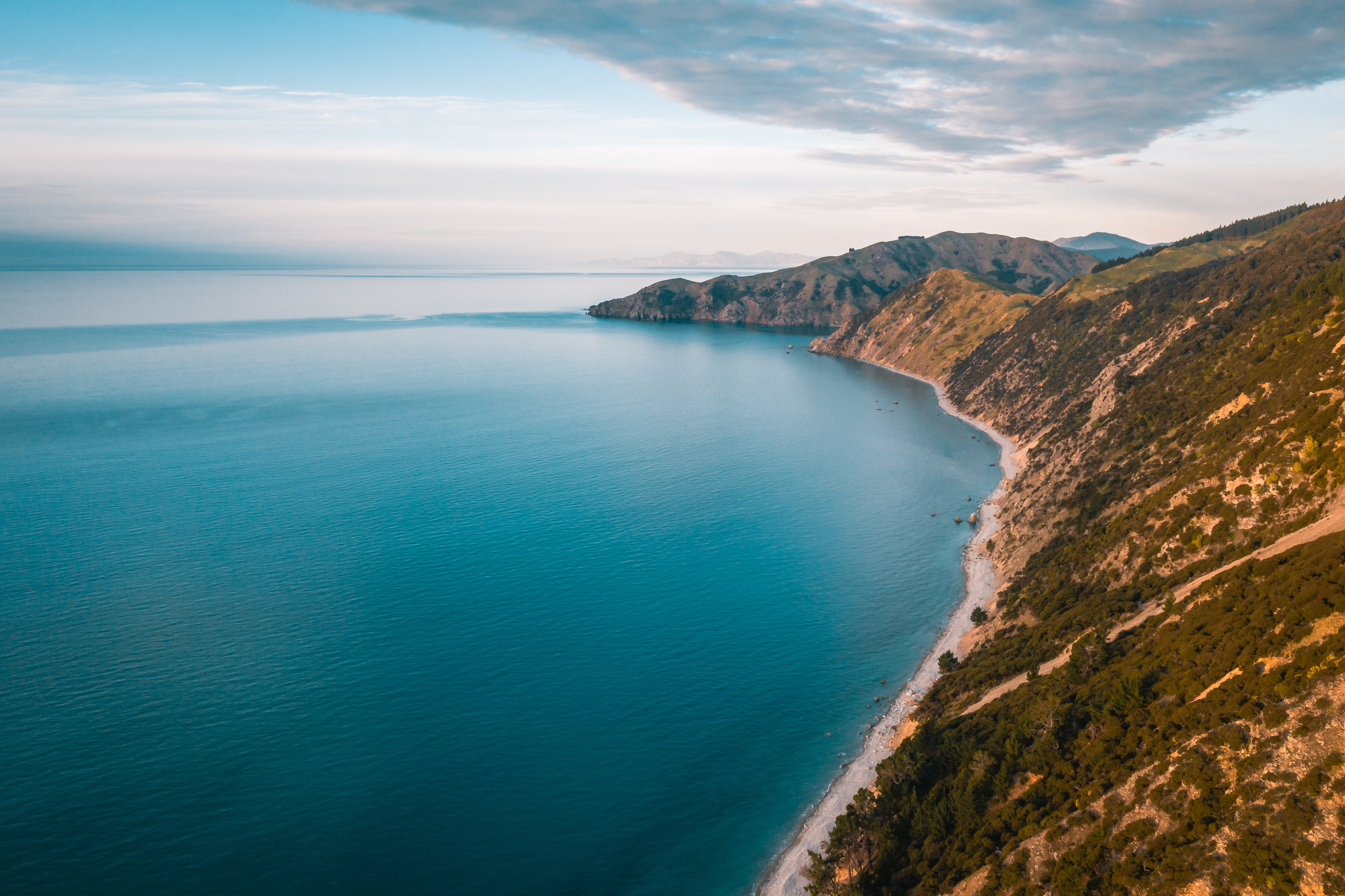 aerial photography of mountain beside blue ocean