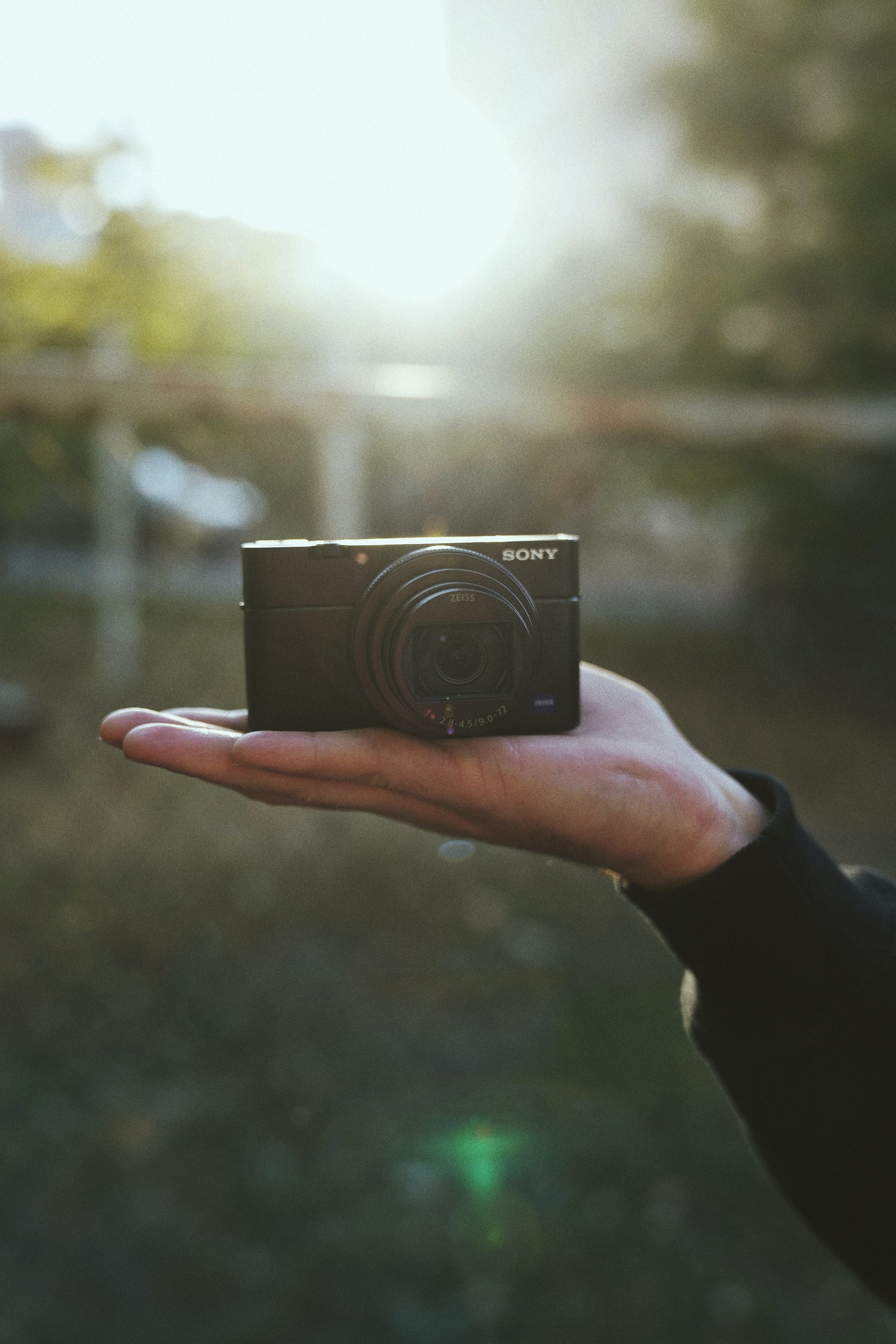 person holding black Sony compact camera