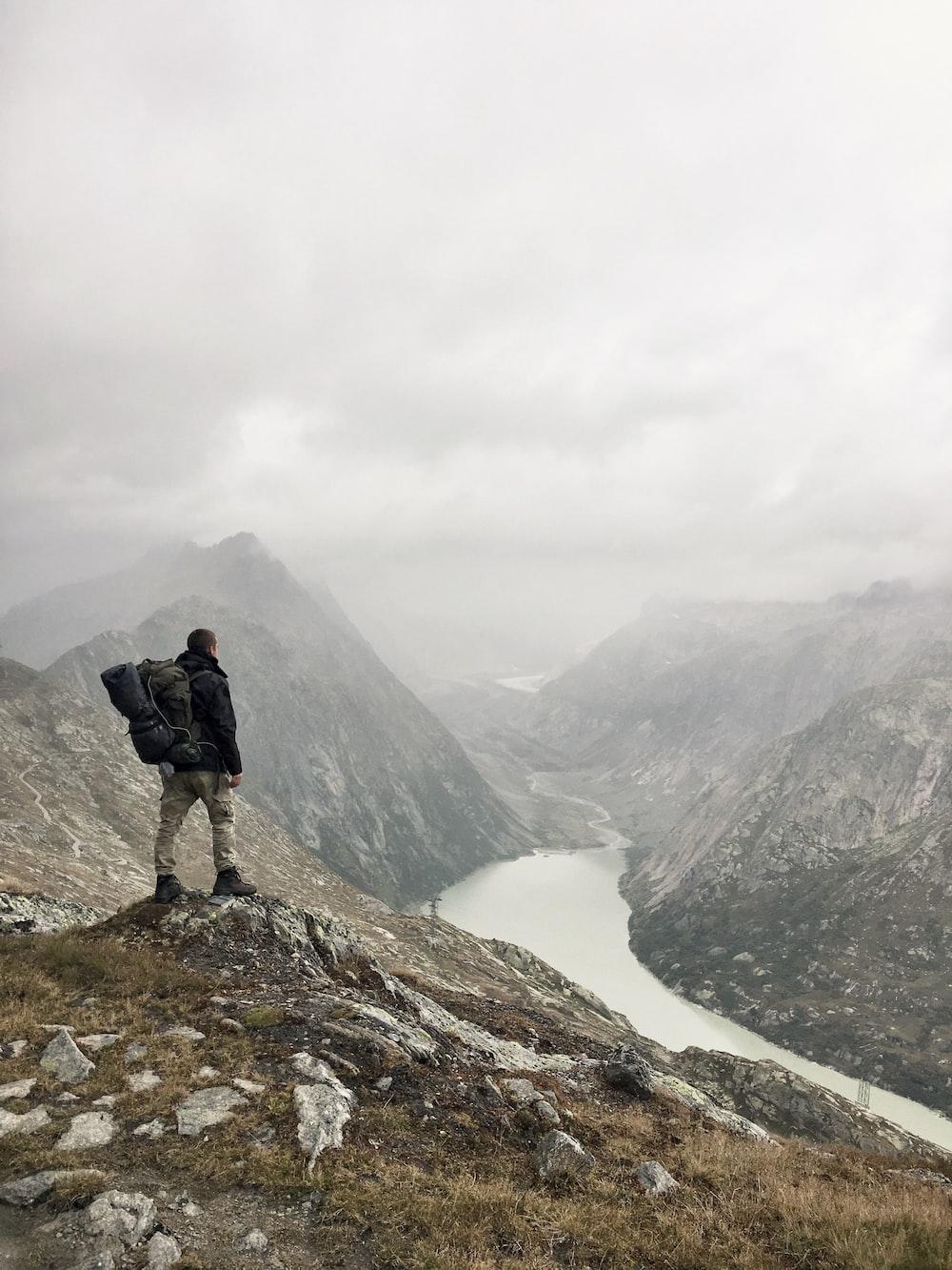 man standing on rock boulder