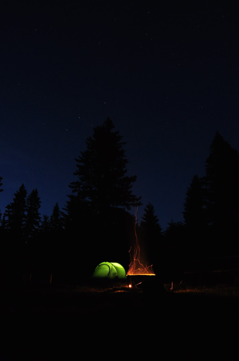 lighted bonfire beside tent at night