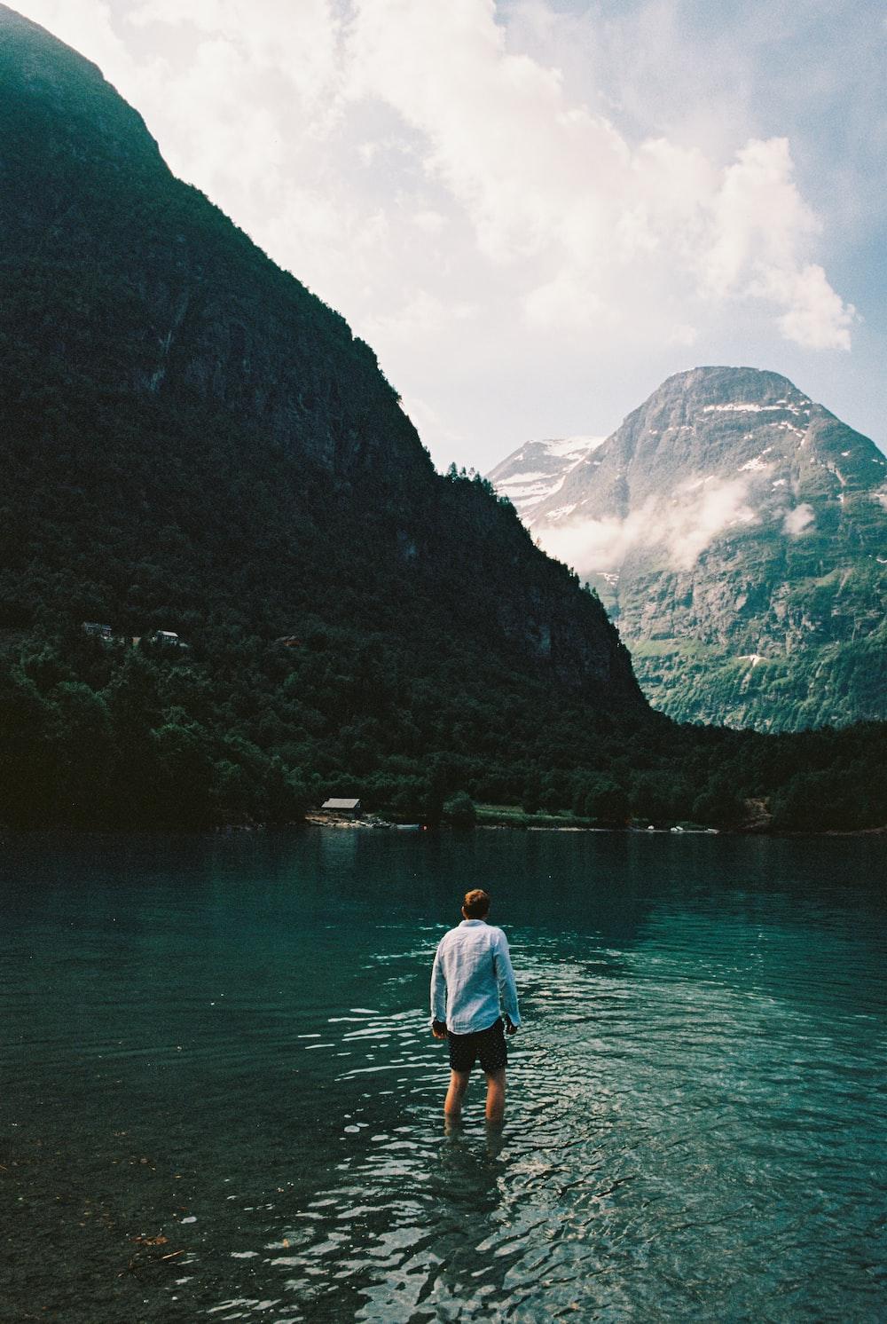 man wearing white dress shirt standing in lake