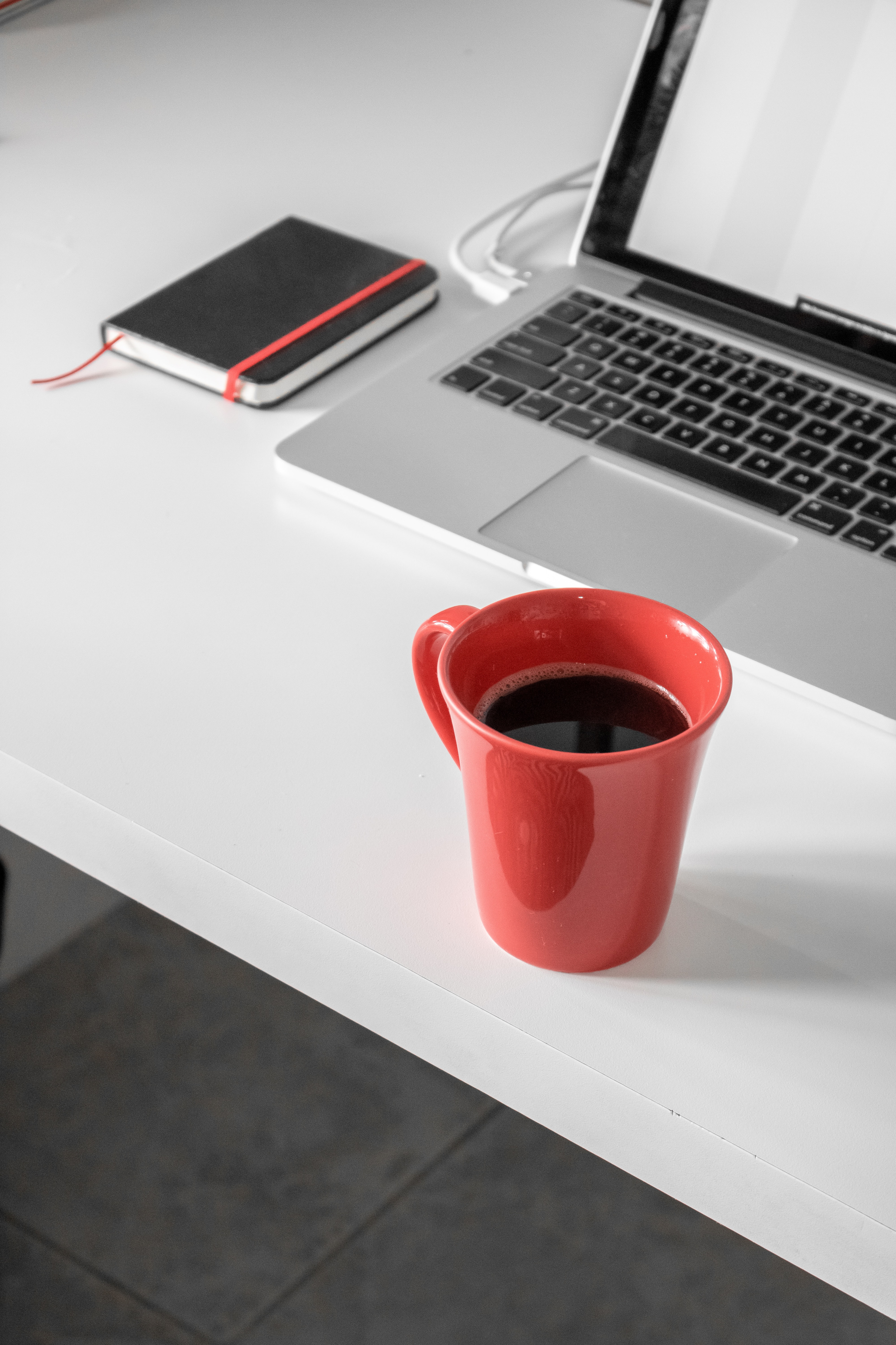 red ceramic mug filled with coffee beside MacBook Pro on white wooden desk