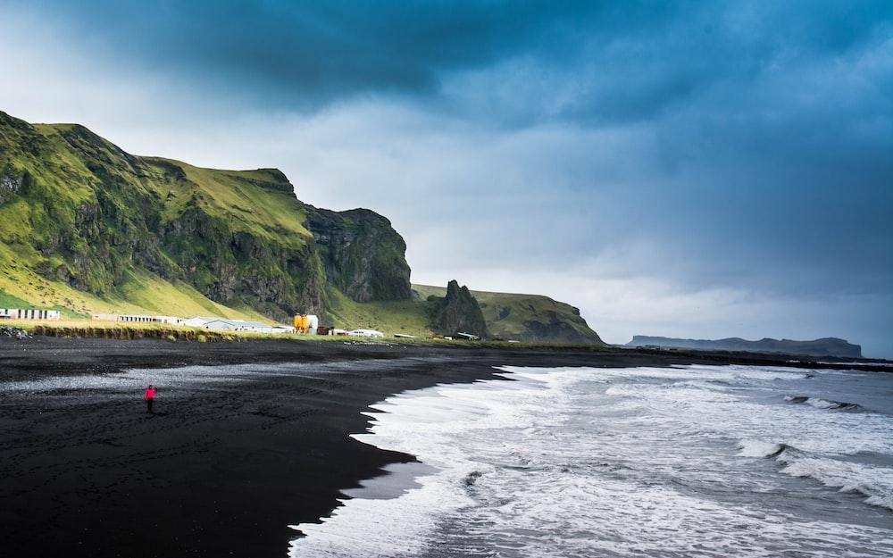 seashore near green mountain under blue sky during daytime