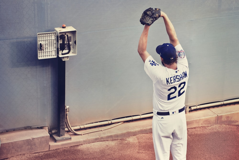 man in white baseball jersey shirt standing with gloves in front of telephone on wall
