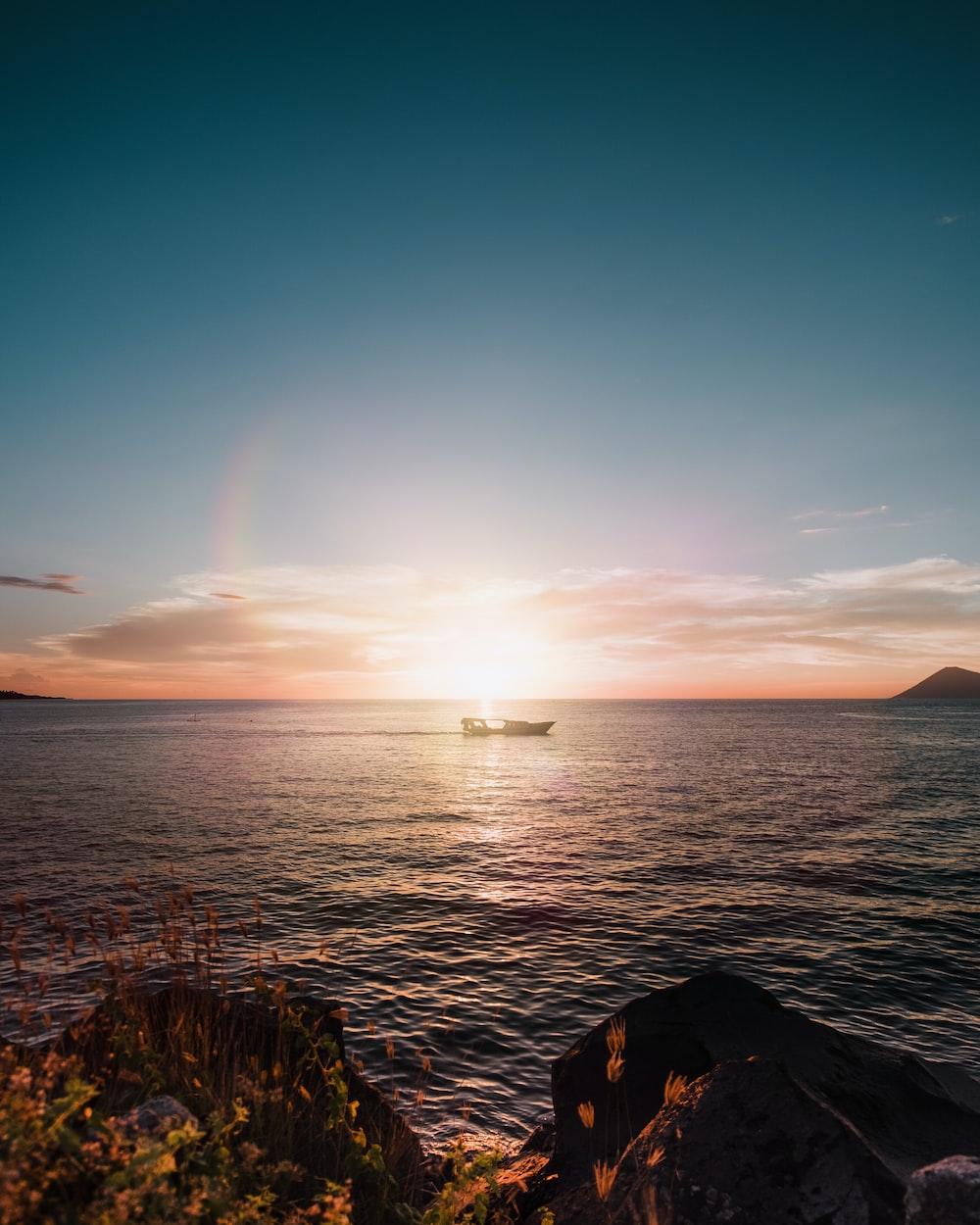 boat on sea near mountain