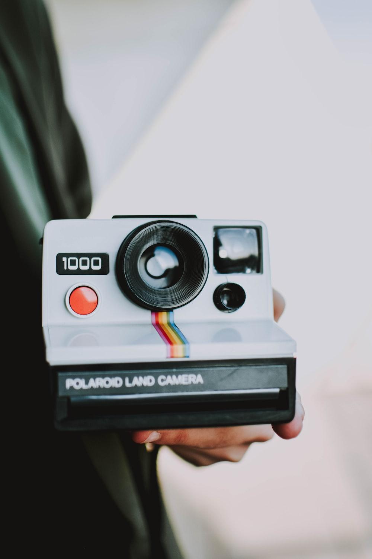 person holding black and white Polaroid land camera