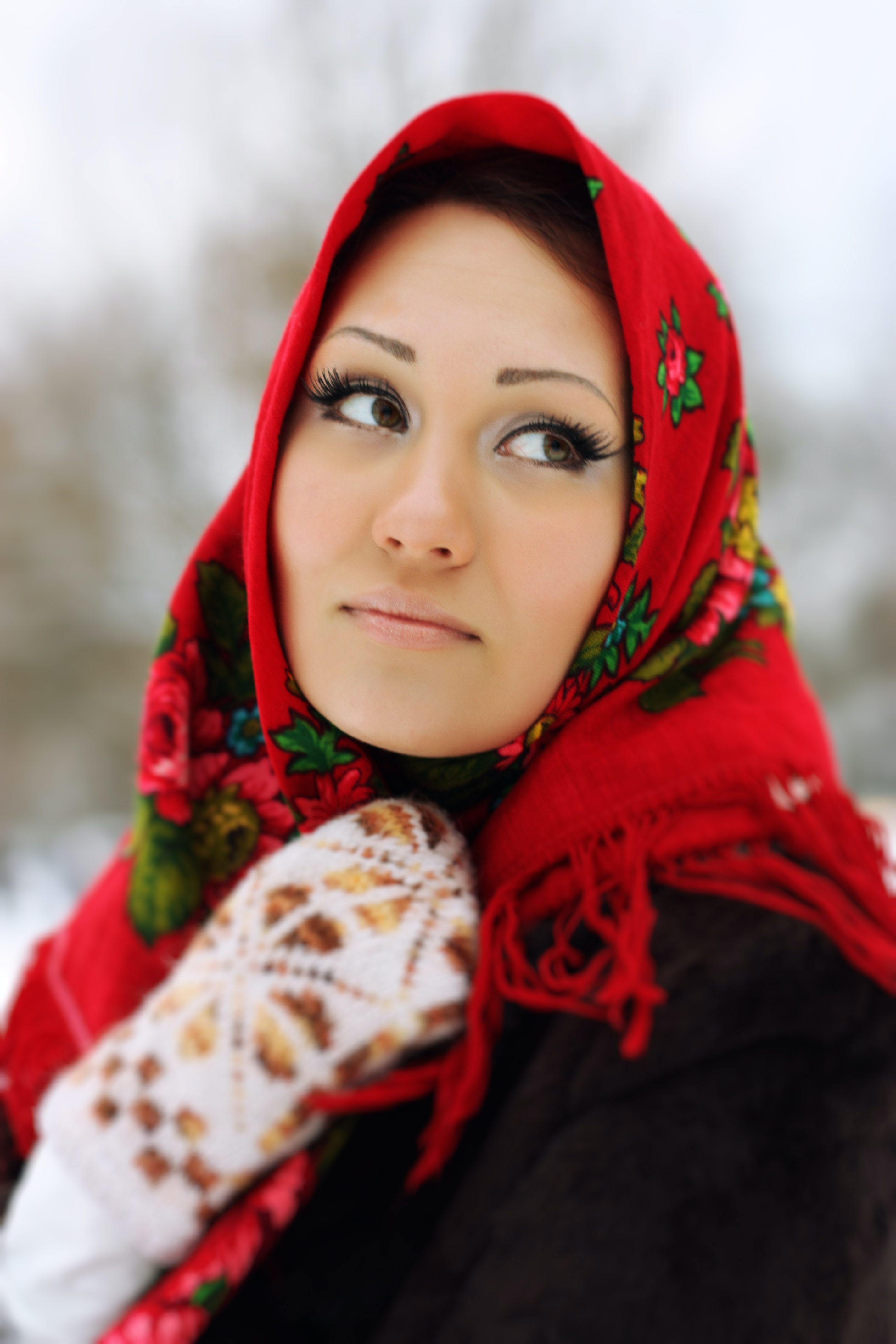 woman in black jacket covering her head with red scarf
