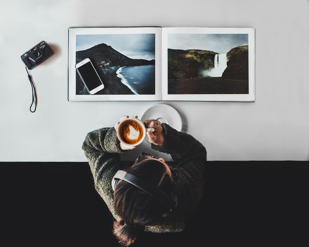 person drinking coffee white listening to headphones
