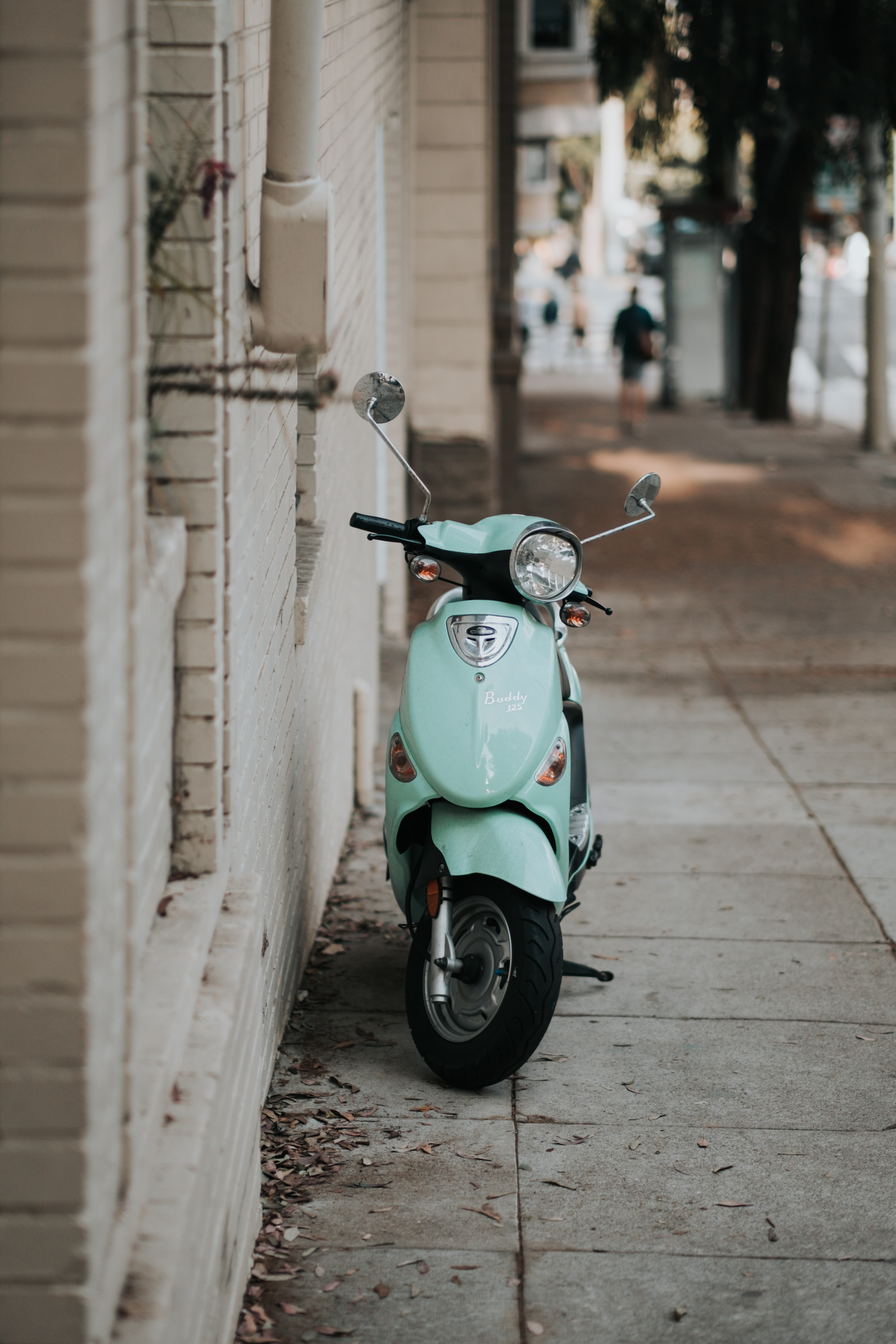 light-blue motor scooter parked near wall
