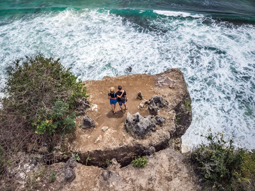 two person standing near the cliff