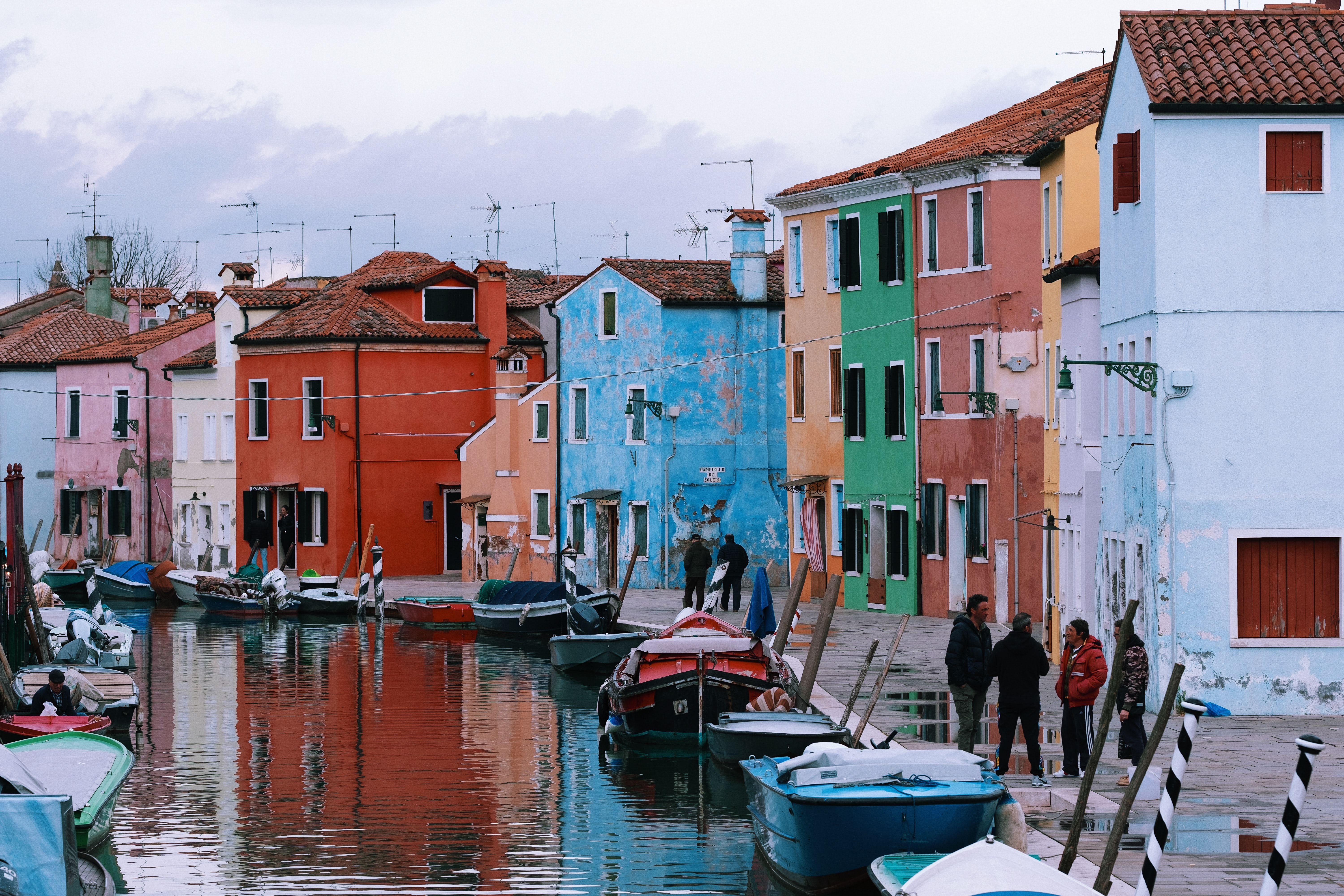 people standing near houses and river during daytime