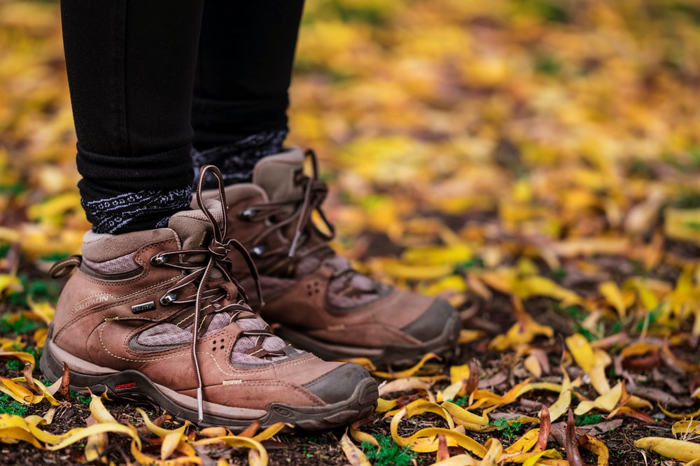 person wearing brown hiking boots