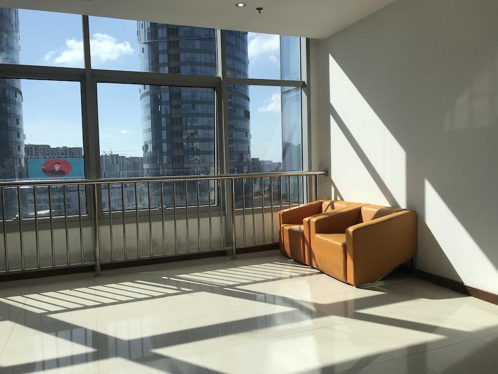 two brown leather sofa chairs beside grey metal railings
