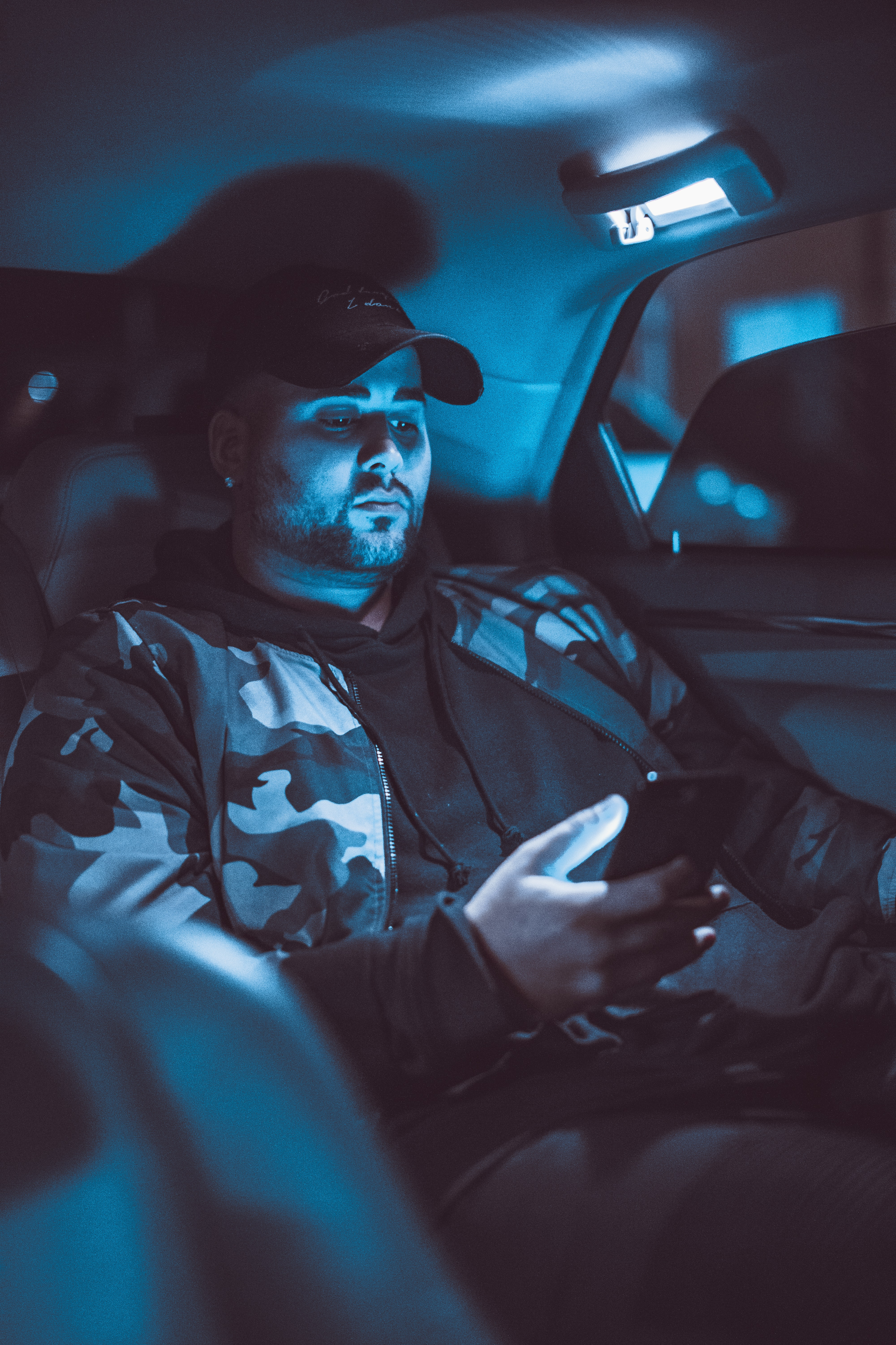 man holding smartphone in vehicle