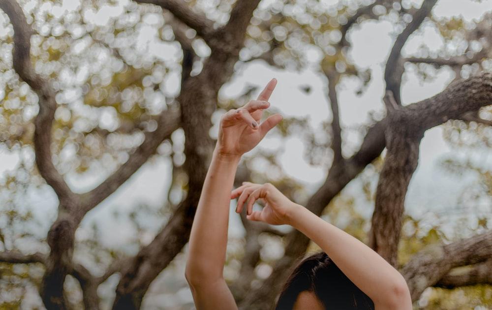 woman raising hands near tree