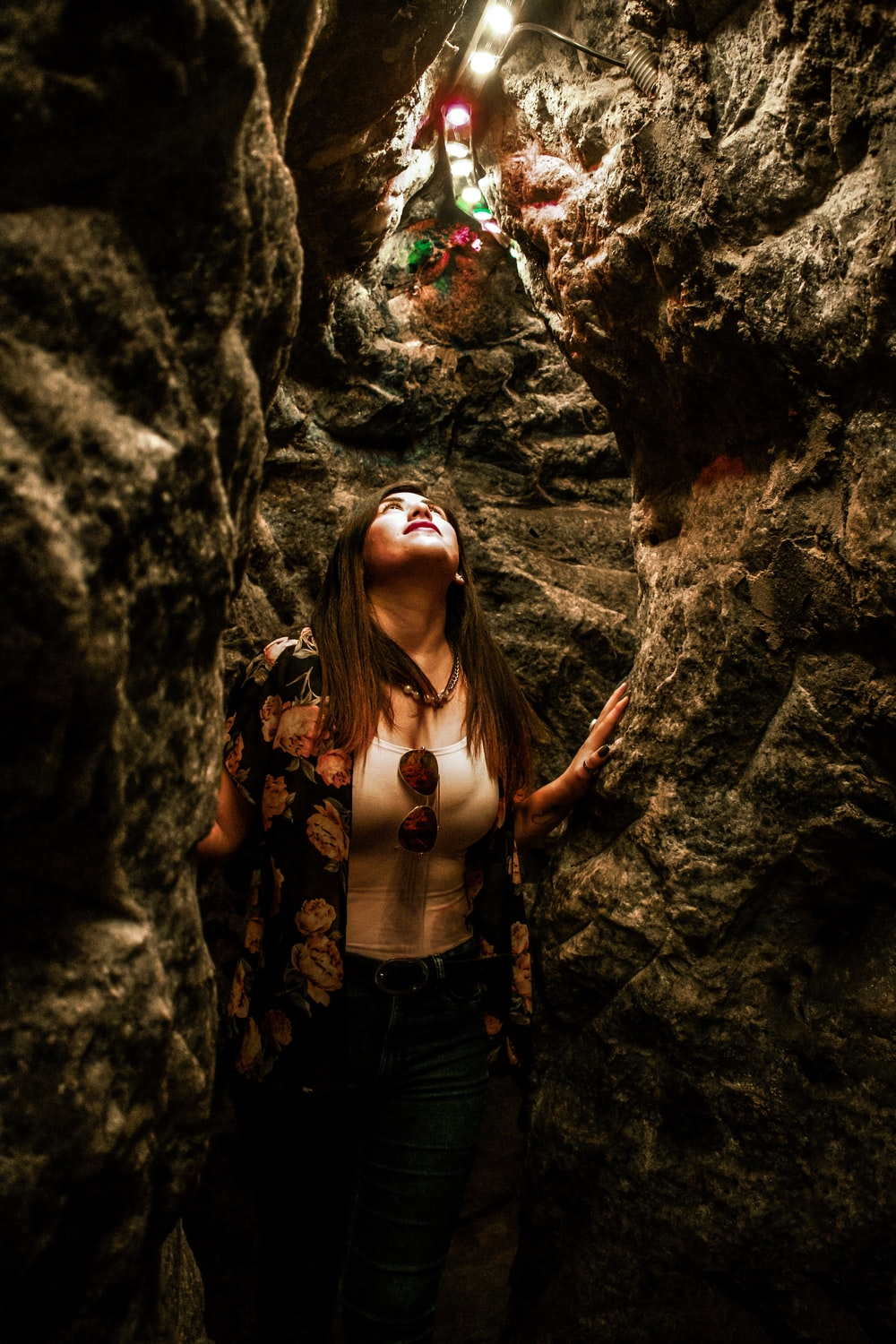 woman looking up while standing inside cave