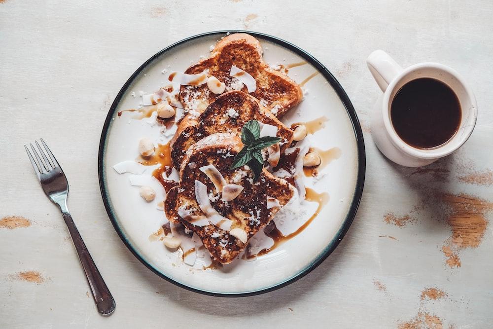 plate of toasted bread beside coffee mug