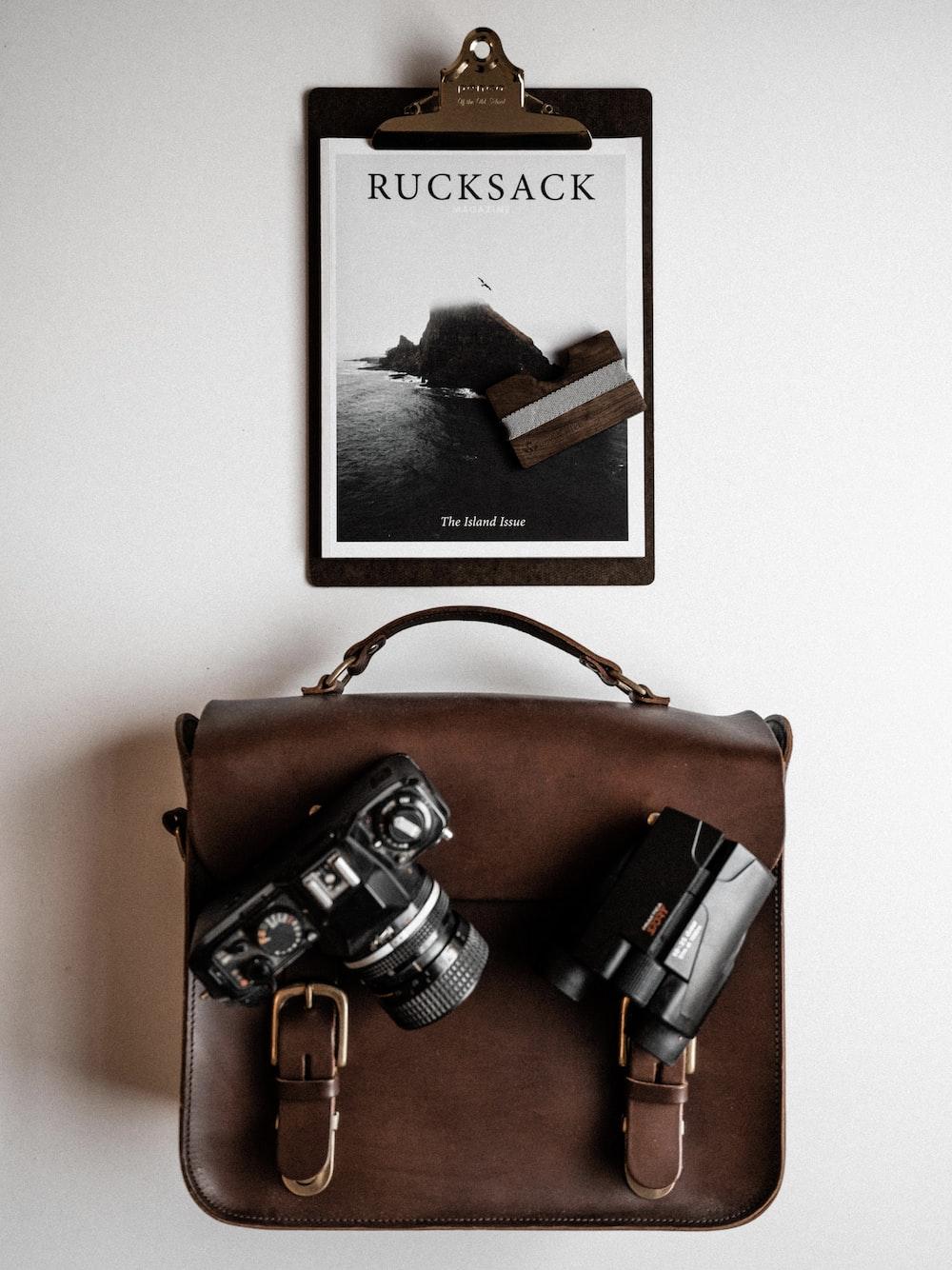 Rucksack paper board and DSLR camera on top of bag